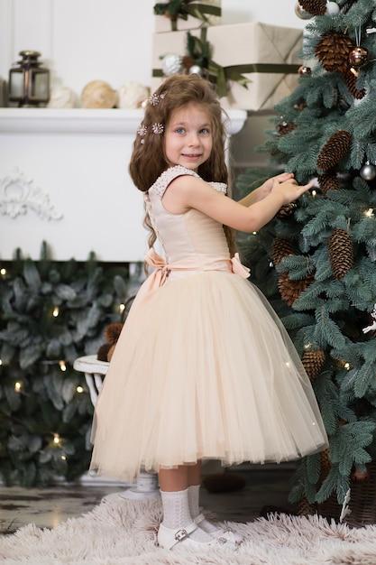 Een schattig klein meisje in een weelderige beige jurk hangt kegels aan de kerstboom die in het huis staat. kerstverhaal, gelukkige jeugd. Premium Foto