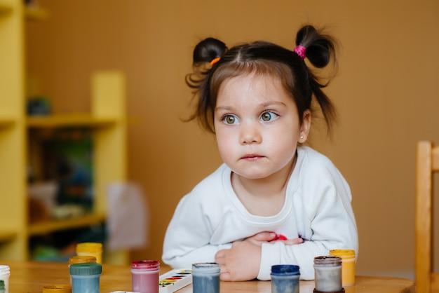 Een schattig klein meisje speelt en schildert in haar kamer. recreatie en amusement. Premium Foto