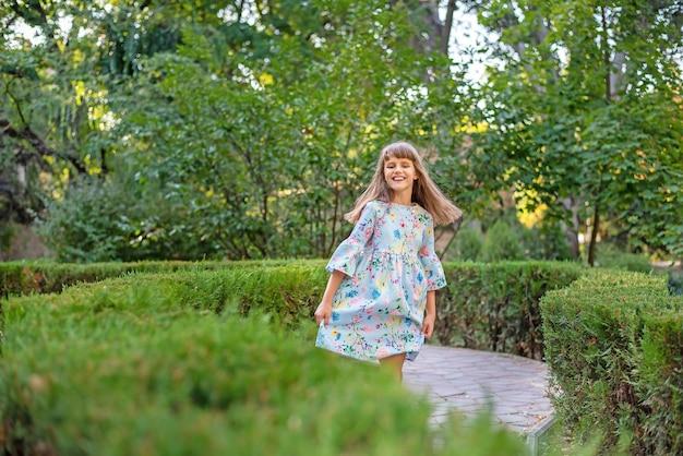 Een schattig klein vrolijk meisje speelt in een groen wirwar van struiken. Premium Foto