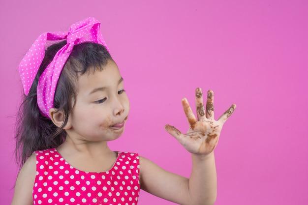 Een schattig meisje dat een rood gestreept shirt draagt dat een chocolade eet met een vuile mond op het roze. Gratis Foto