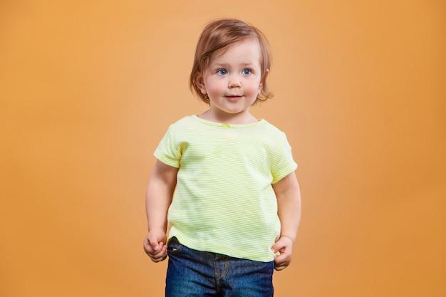 Een schattig meisje op oranje ruimte Gratis Foto