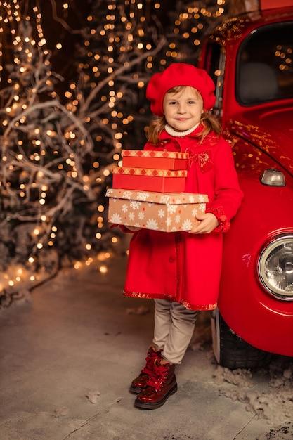 Een schattig vrolijk meisje in een rode baret met nieuwjaarsgeschenken in haar handen in de buurt van een rode auto Premium Foto