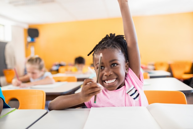 Een schattige leerling hand opsteken Premium Foto