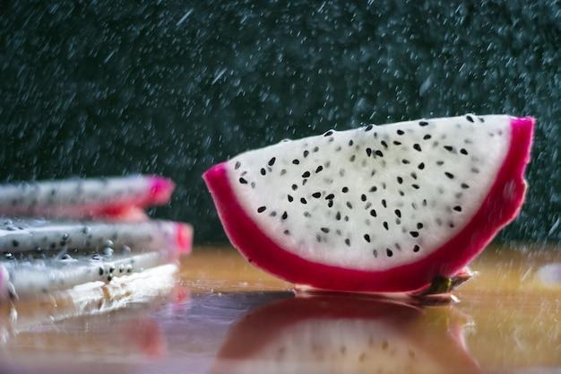 Een scheutje water druppelt in de pitaya Premium Foto