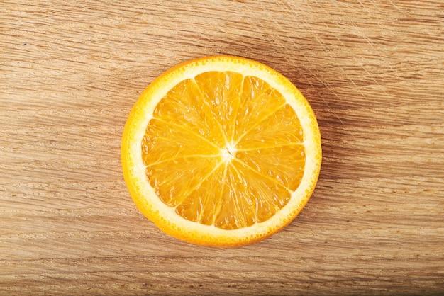 Een schijfje citroen, geïsoleerd op een houten. Gratis Foto
