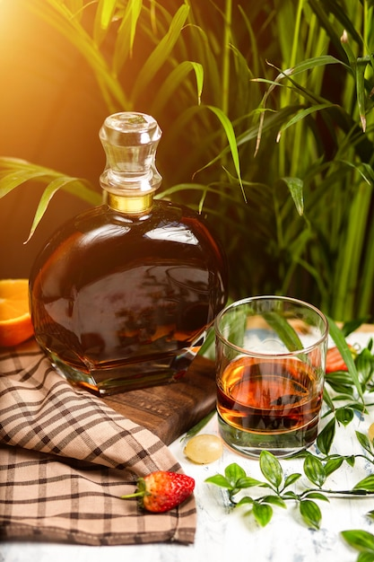 Een schijnwerper op een kristallen glas cognac met fruit en groen, geschoten op een houten tafelblad Gratis Foto