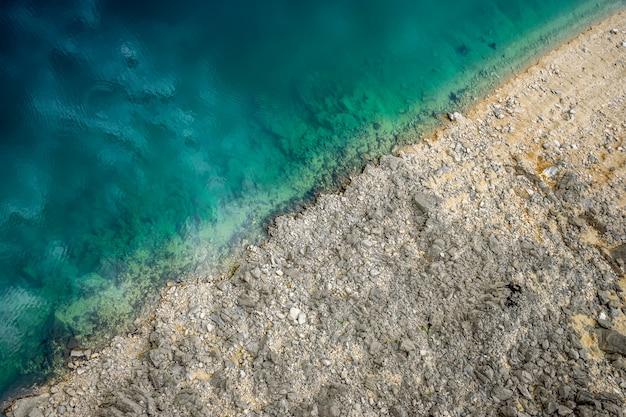 Een schilderachtige plaats waar transparant turkoois water een steenachtige kust ontmoet. Premium Foto