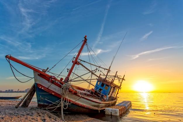 Een schipbreuk verlaten op het strand en het zonlicht tijdens de zon van de tijdzonsondergang Premium Foto