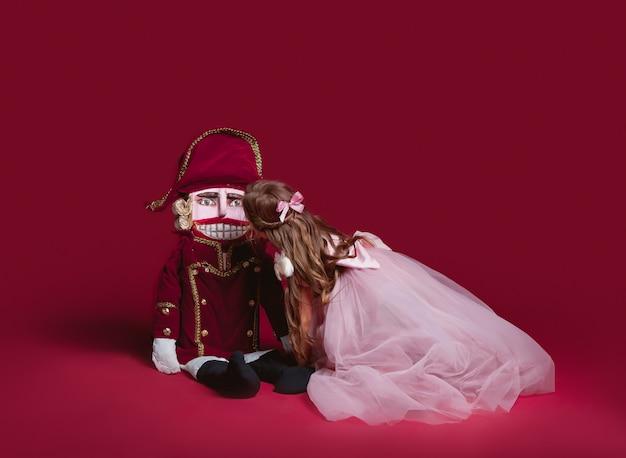 Een schoonheidsballerina die een notekraker houdt bij rode studio Gratis Foto