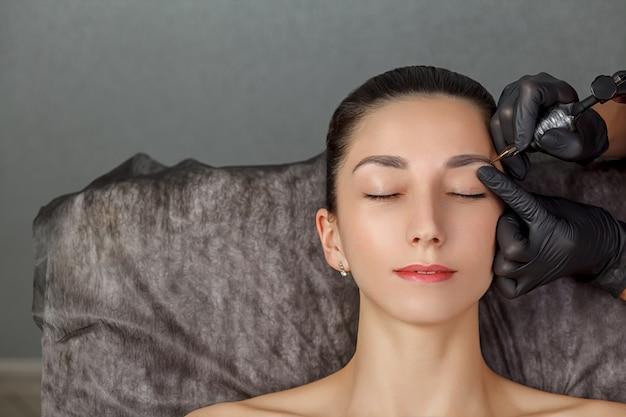 Een schoonheidsspecialiste voert het maken van permanente wenkbrauwen uit. permanente make-upbehandeling. Premium Foto