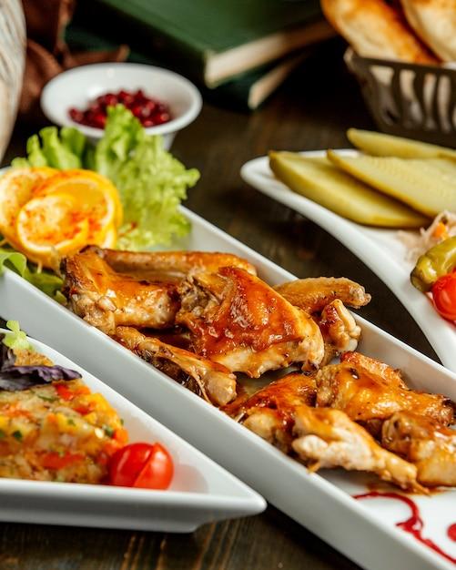 Een schotel van gebakken kippenvleugels gegarneerd met suace Gratis Foto