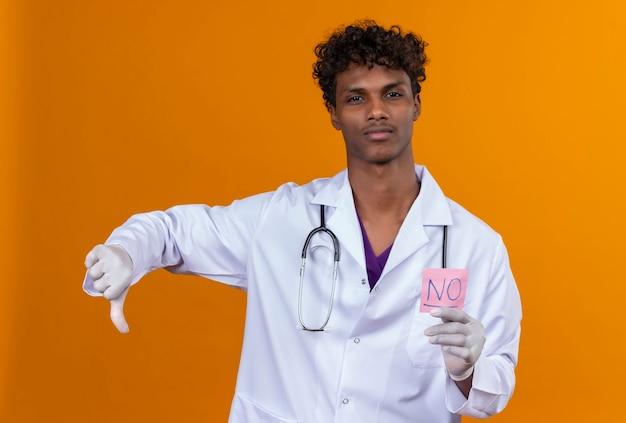Een serieuze jonge knappe donkere man met krullend haar, gekleed in een witte jas met een stethoscoop en een papieren kaart met het woord nee Gratis Foto