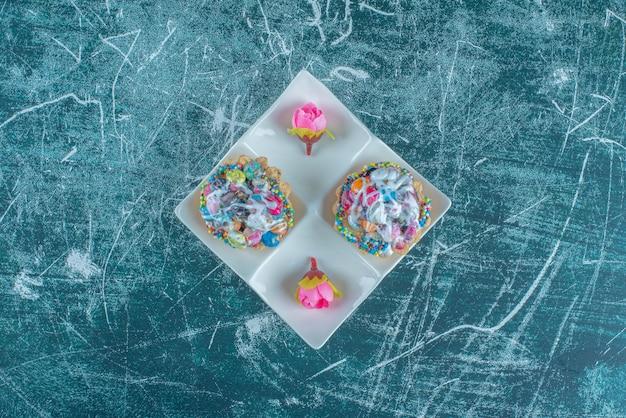 Een serveerschaal met cupcakes en bloemkronen op blauwe achtergrond. hoge kwaliteit foto Gratis Foto