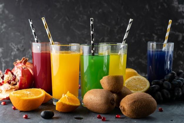 Een set koele verse geperste sappen of cocktails in een glazen gemaakt van sinaasappel, kiwi, citroen, druiven, granaatappels Premium Foto