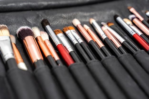Een set zwarte make-upborstels in een zwart lederen etui. Premium Foto