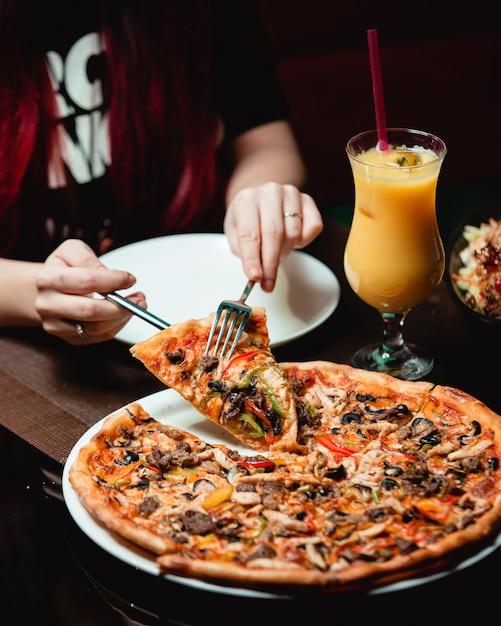 Een sneetje pizza met gemengd ingrediënt nemen met een glas sinaasappelsap. Gratis Foto