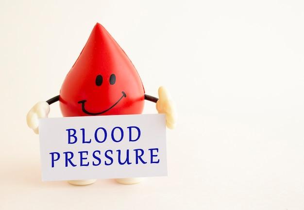 Een speelgoeddruppel bloed bevat een wit visitekaartje met de inscriptie. medisch concept. Premium Foto