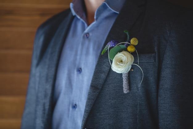 Een speld van roze, witte roos en gele bloemen in de jas van een man. Gratis Foto