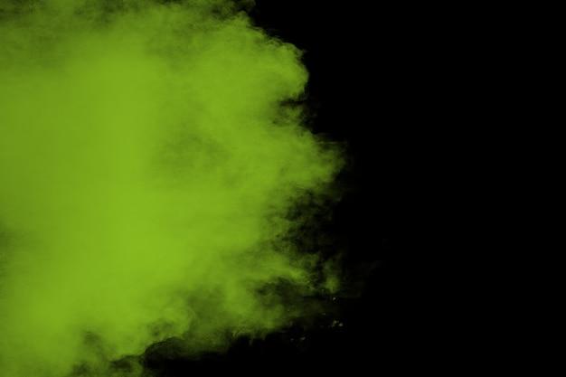 Een splatter van groen gekleurd poeder op zwarte achtergrond. Premium Foto