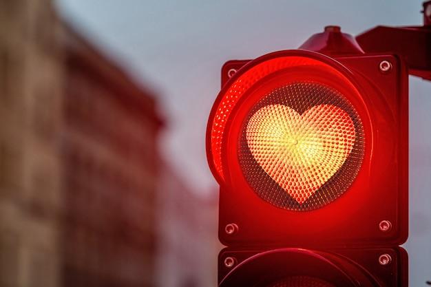 Een stadsovergang met een seinpaal, stoplicht met rode hartvorm in seinpaal Premium Foto