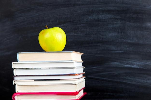 Een stapel boeken, bovenop een appel, tegen een zwart bord, exemplaarruimte. Premium Foto