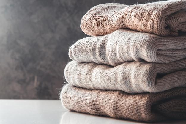 Een stapel gebreide truien, het concept van warmte en comfort, hobby, achtergrond, close-up Premium Foto