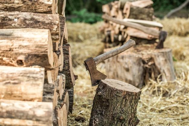 Een stapel gestapelde boomstammen en een bijl Gratis Foto