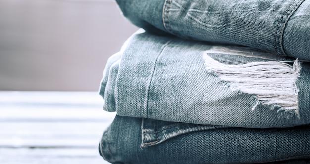 Een stapel jeans op een houten achtergrond Gratis Foto