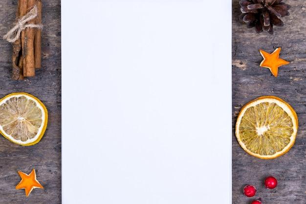 Een stapel kaneelstokjes, gedroogde sinaasappel en mandarijnsterren op oude houten tafel met wit leeg vel papier. kerst decoratie. kerstkaart Premium Foto