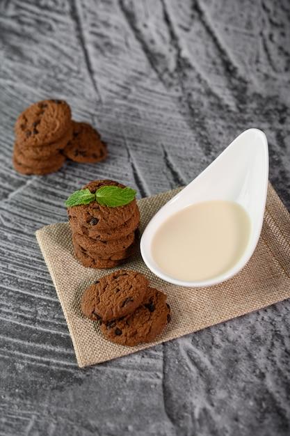 Een stapel koekjes en een lepel melk op een doek op een houten tafel Gratis Foto