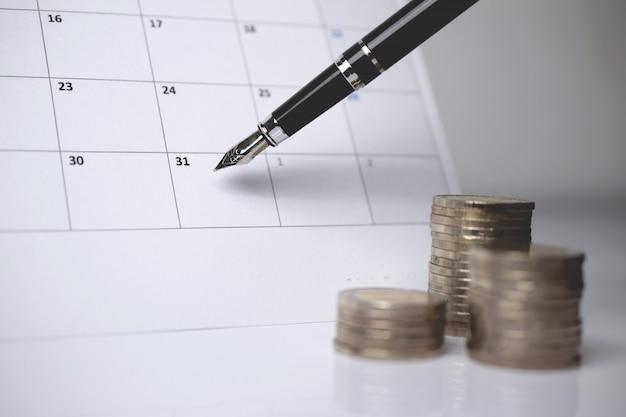 Een stapel munten en een pen op de kalender. Premium Foto