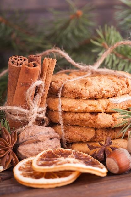 Een stapel notenkoekjes, kaneel, badon, sinaasappels, noten. feestelijke traktatie, kerstmis. Premium Foto