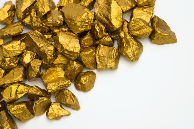 Een stapel van goudklompjes of gouderts geïsoleerd op wit Premium Foto