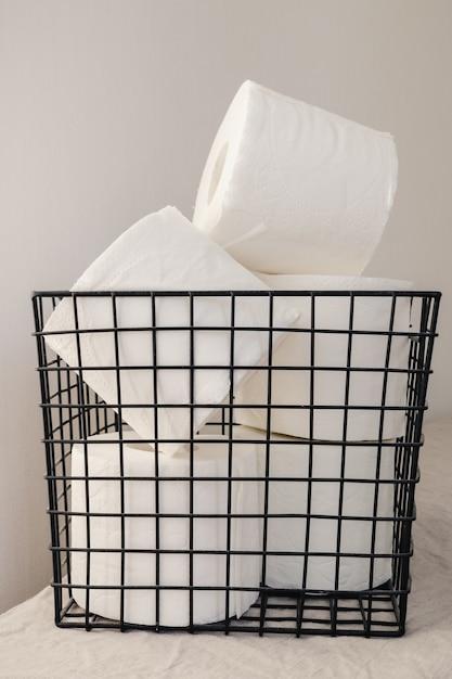 Een stapel wc-papierrollen georganiseerd in een zwarte metalen mand op een wit oppervlak. minimaal interieurconcept Premium Foto