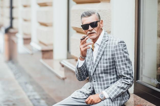 Een stijlvolle oude man roken sigaret, grijs pak dragen. close-up Premium Foto