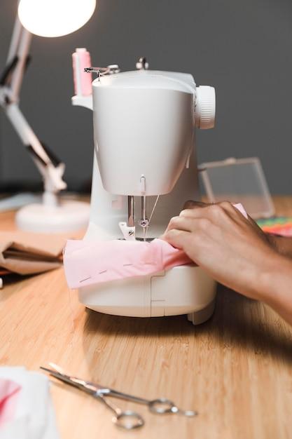 Een stoffen masker maken met het vooraanzicht van de naaimachine Gratis Foto
