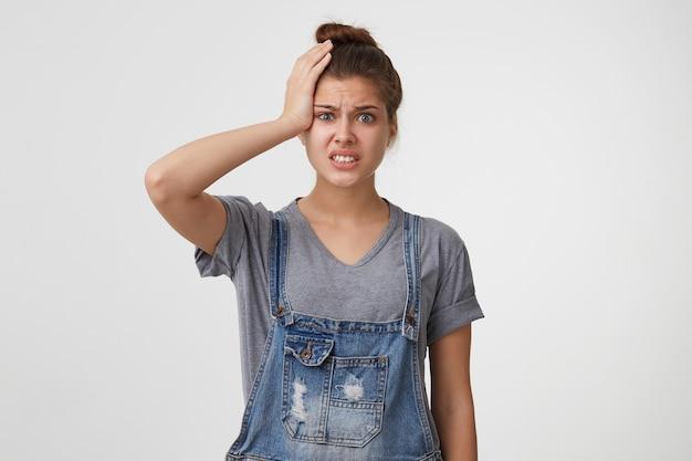 Een stressvolle vrouw in een spijkerbroek klampte zich in paniek aan haar hoofd Gratis Foto