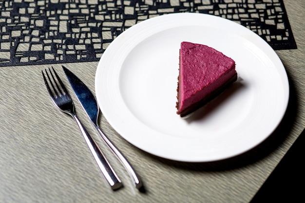 Een stuk frambozenkaastaart in witte plaat diende op de tafel Gratis Foto
