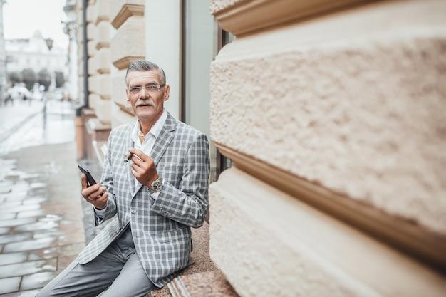 Een succesvolle oude man van de zomerdag met cubaanse sigaret die naar de camera kijkt Premium Foto