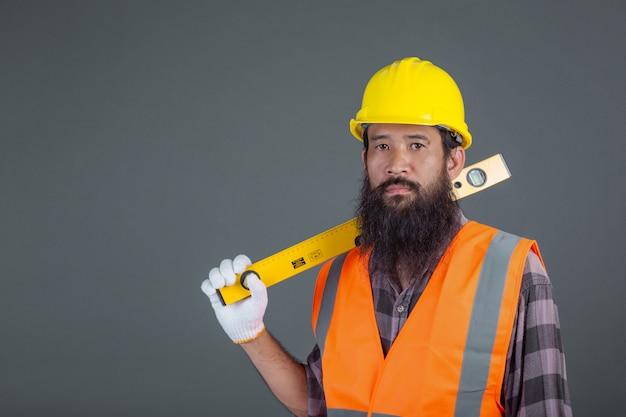 Een technische man die een gele helm draagt die een waterspiegelmeter op grijs houdt. Gratis Foto