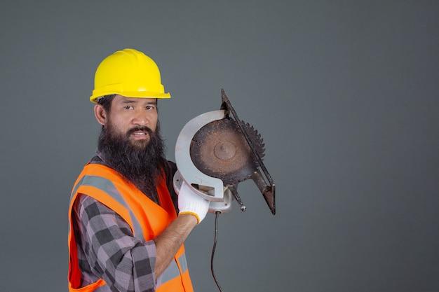 Een technische man draagt een gele helm met bouwmachines op een grijze. Gratis Foto