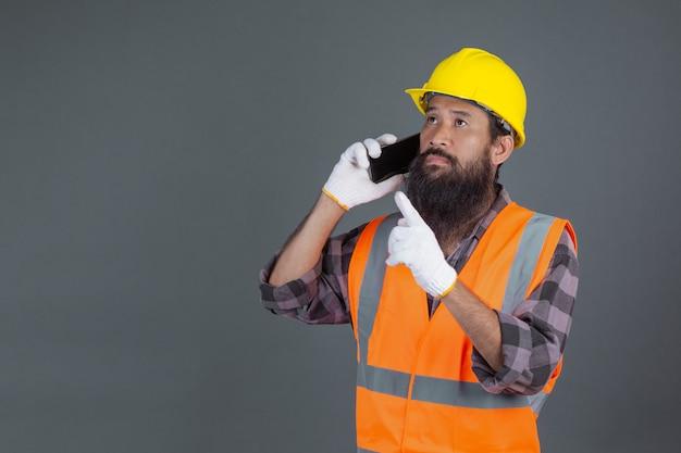 Een technische man draagt een gele helm met een telefoon op een grijze. Gratis Foto