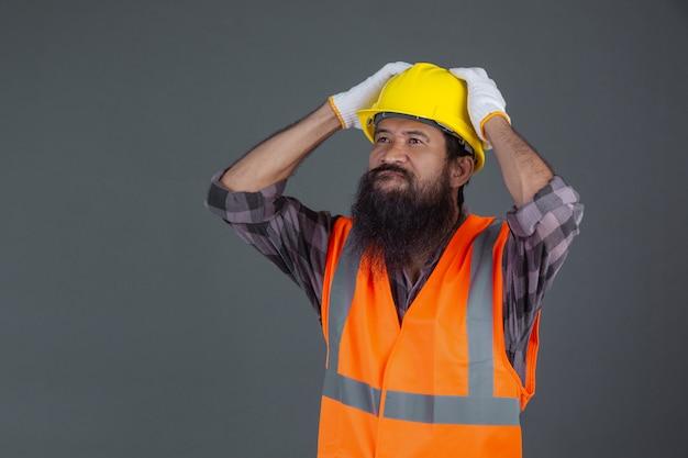 Een technische man met een gele helm met witte handschoenen toonde een grijs gebaar. Gratis Foto