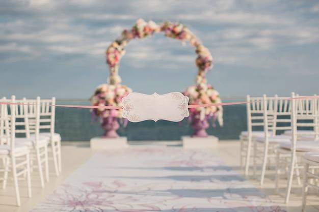 Een teken op de achtergrond van huwelijksboog en de zee. Premium Foto