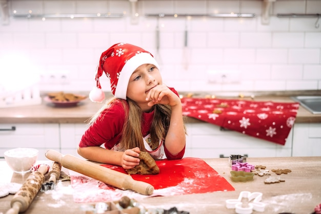 Een tienermeisje staat in de keuken aan de tafel en bereidt deeg voor bakken Premium Foto