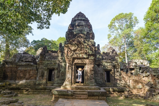 Een toerist bezoekt angkor ruïnes te midden van de jungle, angkor wat tempelcomplex, reisbestemming cambodja. vrouw met traditionele hoed, achteraanzicht. Premium Foto