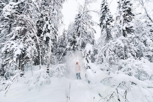 Een toerist loopt in een met sneeuw bedekt bos. winterbos in estland. reis door het winterbos. Premium Foto