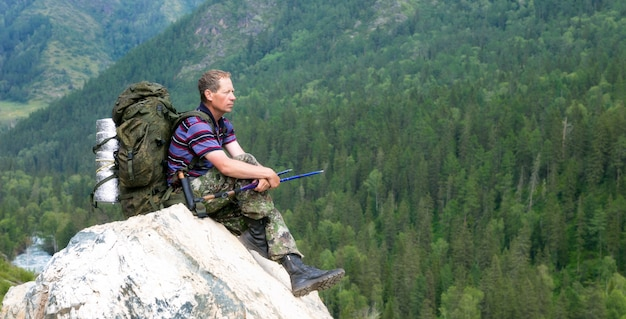 Een toerist op een hoge berg kijkt naar de natuur. Premium Foto