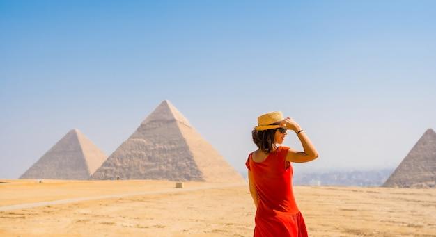Een toeristisch meisje in een rode jurk kijkt naar de piramides van gizeh, het oudste grafmonument ter wereld. in de stad caïro, egypte Premium Foto
