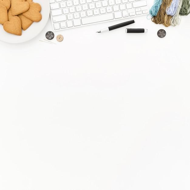 Een toetsenbord, een bord met koekjes, wat draad en knoppen op een wit oppervlak Gratis Foto